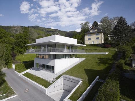 Stunning views define austrian home cut into hillside for Hillside architecture