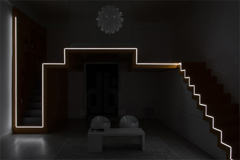 the entire orange stair assembly is highlighted with a strip of lights snaking across its edge at night the lights illuminate the apartment in a geometric
