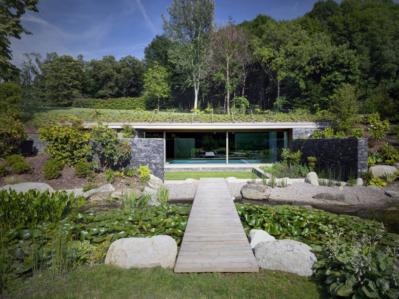 Hidden oasis green roofed indoor pool leads to sunken for Migliori progetti di pool house