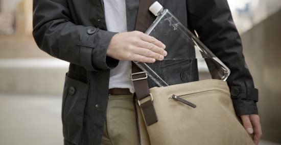 A slim waterbottle being tucked into a bag.