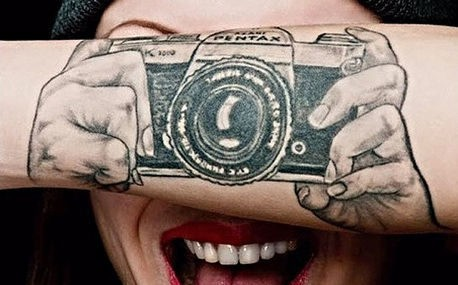 camera' tattoo in front of face